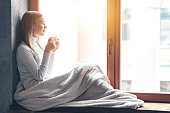 Side view of beautiful young woman holding coffee cup and looking through window while sitting at windowsill at home
