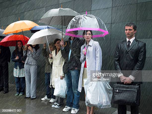 Soaked businessman standing beside group of people under umbrellas