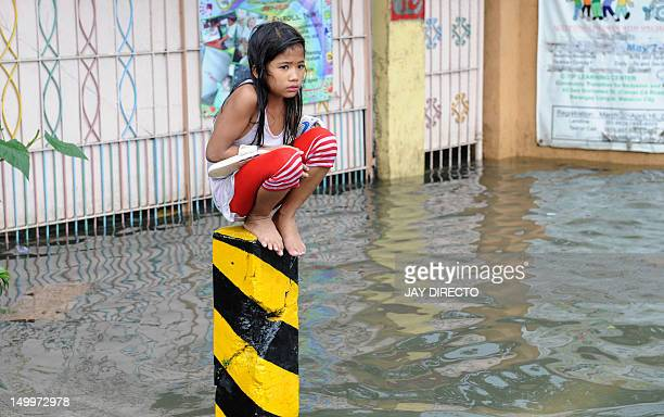 A soaking wet child sits on a post on a flooded street in suburban Manila on August 8 2012 More than one million people in and around the Philippine...