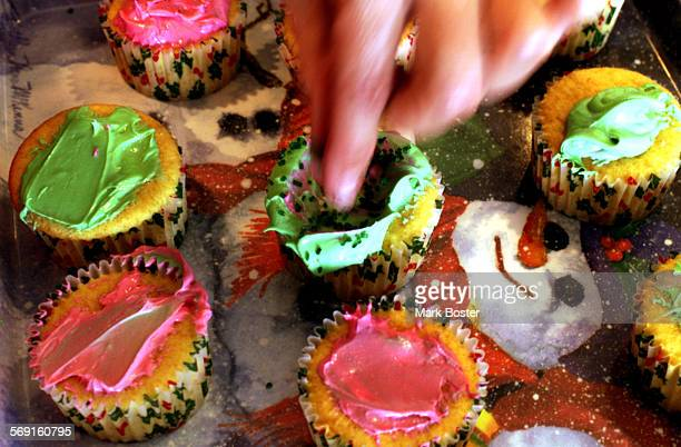 SOAllergicCakes120799MB–––DrLauralyn Markle and her daughter Kelly6 decorating a tray of holiday cupcakes Kelly is so allergic to food containing...