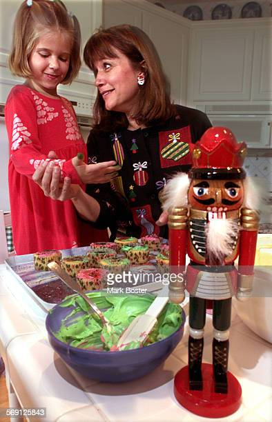 SOAllergicCook120799MB–––DrLauralyn Markle and her daughter Kelly6 in their festively decorated kitchen decorating a tray of holiday cupcakes Kelly...