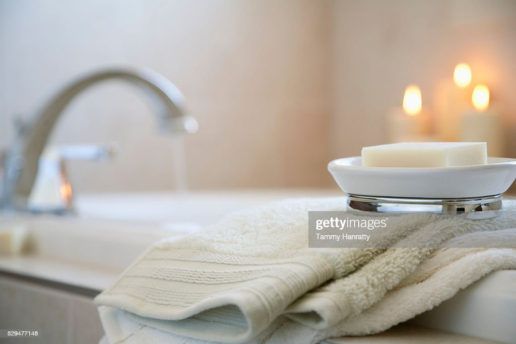 Soap and towels on edge of bathtub : Bildbanksbilder