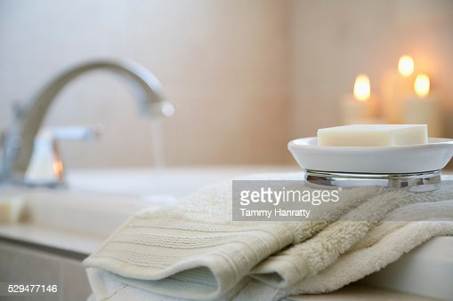 Soap and towels on edge of bathtub : Stock Photo