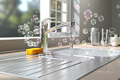 A lot of soap bubbles floating in the air at a kitchen environment washing dishes.