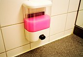 A soap dispenser filled with pink liquid soap