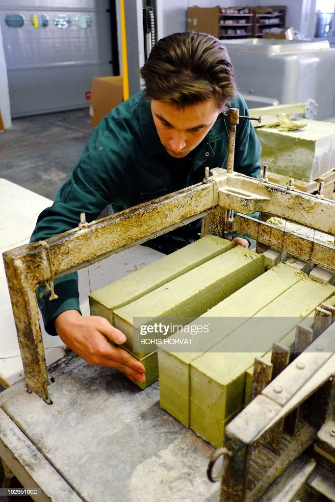 A soap-maker lines up blocks of Marseille Soap (Savon de Marseille) to cut on February 26, 2013 in Salon-de-Provence, southern France. The four remaining Marseille soap-makers, who estimate that their product is too often victim to unfair competition by inathentenic products, are cleaning up the market to defend their product, firstly with a collective brand, and soon, they hope, with a 'geographic indication'. 'There is more fake Marseille soap being sold than real' claims Julie Bousquet-Fabre, the president of the Union of professionals of Marseille soap (UPSM).
