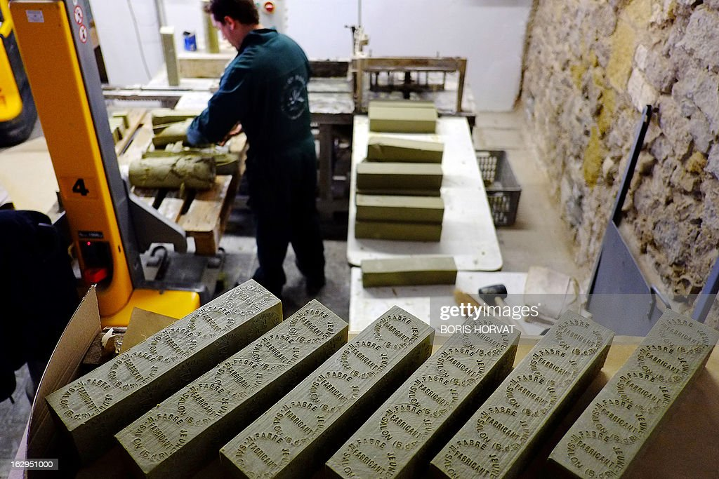 A soap-maker stacks bars of Marseille Soap (Savon de Marseille) on February 26, 2013 in Salon-de-Provence, southern France. The four remaining Marseille soap-makers, who estimate that their product is too often victim to unfair competition by inathentenic products, are cleaning up the market to defend their product, firstly with a collective brand, and soon, they hope, with a 'geographic indication'. 'There is more fake Marseille soap being sold than real' claims Julie Bousquet-Fabre, the president of the Union of professionals of Marseille soap (UPSM).