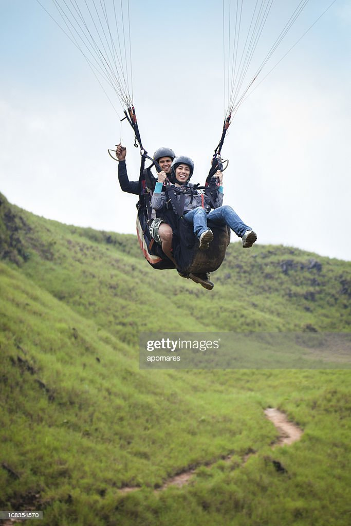 Soaring - Young couple doing tandem paragliding : Stock Photo