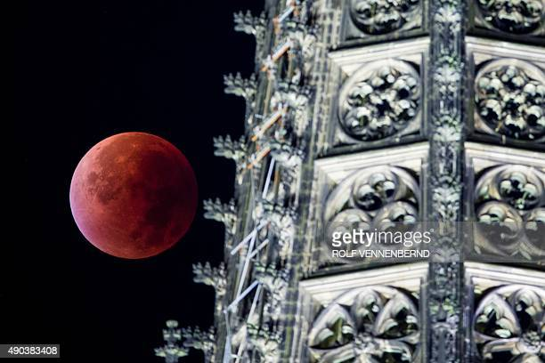 A socalled 'blood moon' can be seen behind one of the steeples of the Cologne Cathedral during a total lunar eclipse in Cologne western Germany on...