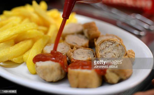 Socalled Currywurst sausages are prepared at the Ziervogels Kult Curry restaurant on July 16 2012 in Berlin Currywurst a Berlin street foodstalls...