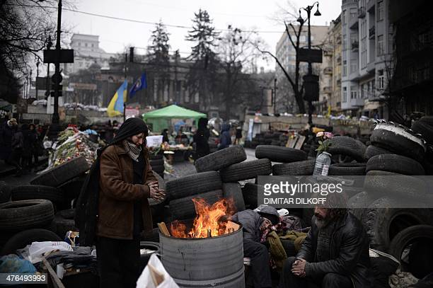 A socalled Maidan self defence unit member warms by a stove at a barricade near the Dinamo stadium close to Independence square in central Kiev on...