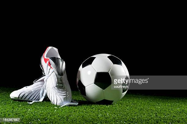 Soccer ball and boots on grass
