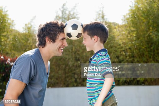 Soccer ball between father and son : Stock Photo