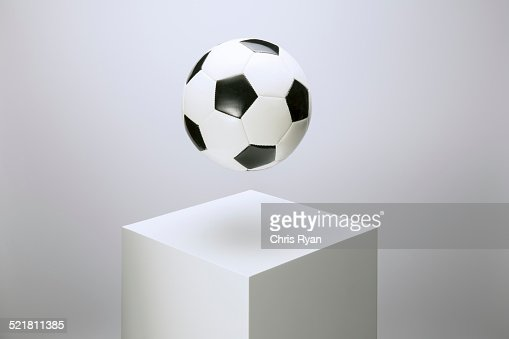 Soccer ball hovering over pedestal