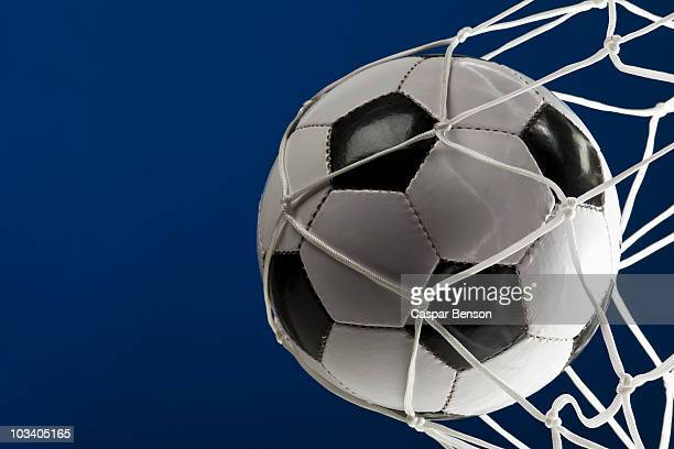 A soccer ball in a net, close-up