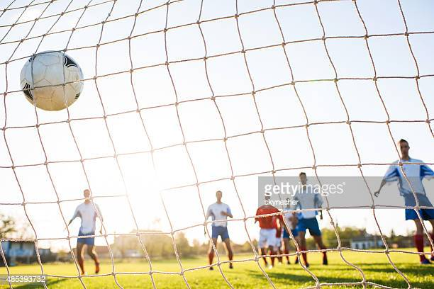 Soccer ball in goalkeeper's net.