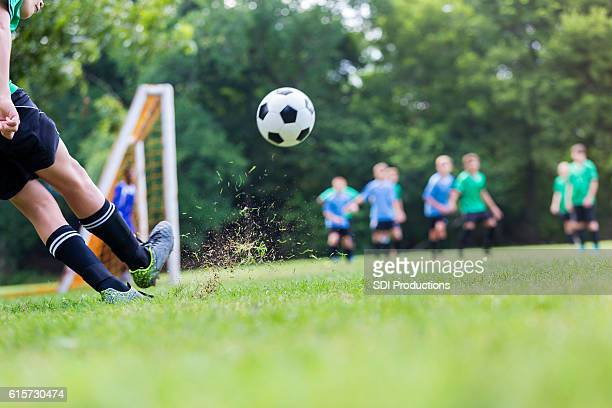 Soccer ball is in mid air while player takes shot
