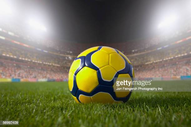 Soccer ball resting on grass in large stadium