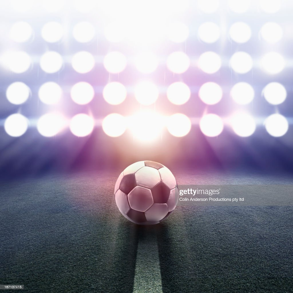 Soccer ball rolling towards stadium lights : Stock Photo
