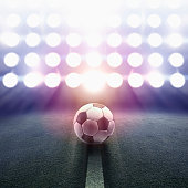 Soccer ball rolling towards stadium lights