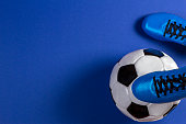 Soccer ball under soccer players feet on blue background.