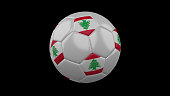 Soccer ball with the flag of Lebanon colorson black background, 3d rendering
