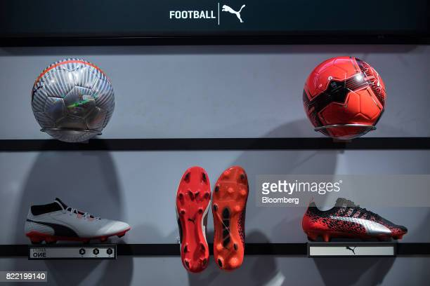 Soccer boots and footballs sit on display inside a Puma SE sportswear clothing store in Berlin Germany on Tuesday July 25 2017 Puma increased its...