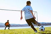 Soccer boy taking shot at goal, goalkeeper watching