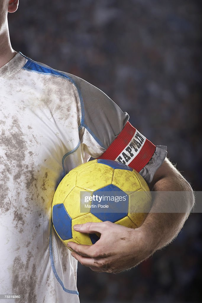 Soccer captain holding ball underarm, close up of ball