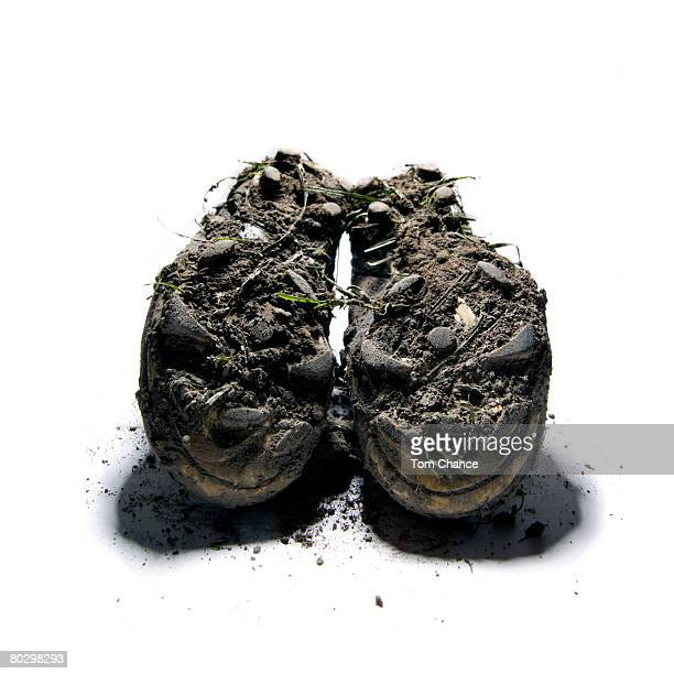 Pair of muddy boots on white background, close-up