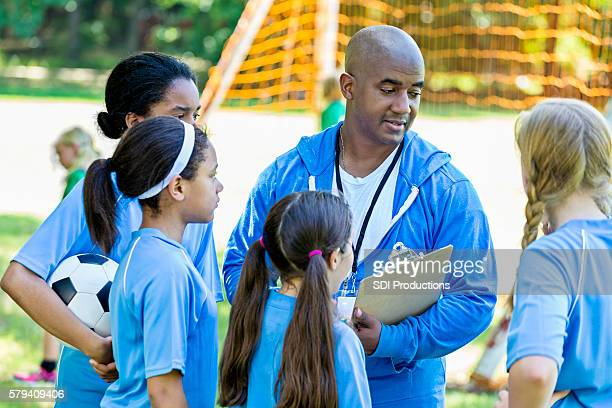 Soccer coach discussing plays with his girls soccer team