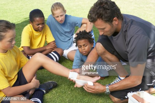 Soccer coach showing children (9-12) first aid : Stock Photo