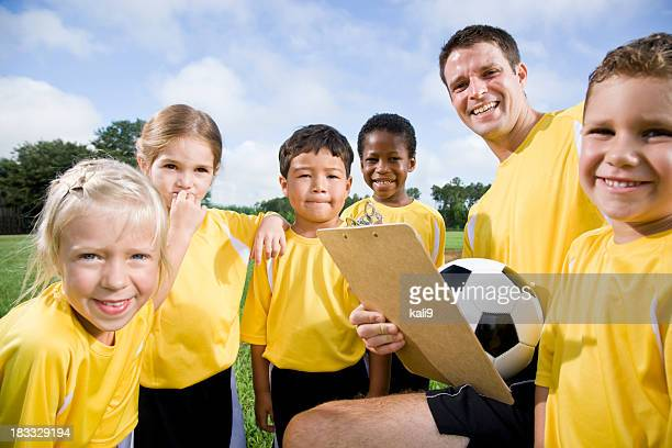 Soccer coach with team of young children