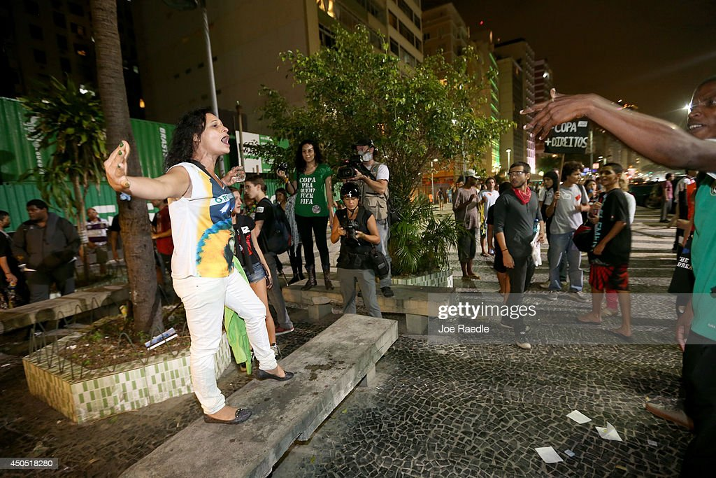 A soccer fan (L) and anti-World Cup protestors yell at each other at a restaurant that was showing the game on Copacabana beach on June 12, 2014 in Rio de Janeiro, Brazil. Brazil defeated Croatia 3-1 in the first match of 2014 FIFA World Cup today.