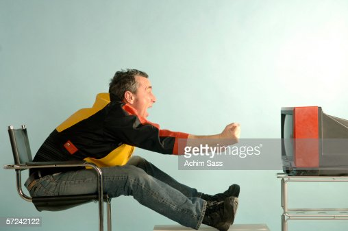 man cheering in front of tv side view stock foto getty images. Black Bedroom Furniture Sets. Home Design Ideas