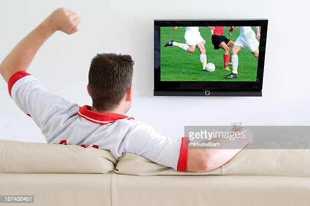 Soccer fan watches a football match on tv and cheers