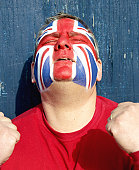 Soccer fan with face painted as Union flag, head tilted back