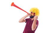 Soccer fan with wig and vuvuzela celebrating