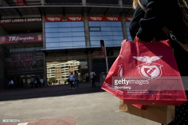 Soccer fans carry bags of merchandise and souvenirs at Sport Lisboa e Benfica's Luz stadium in Lisbon Portugal on Thursday April 27 2017 Portuguese...