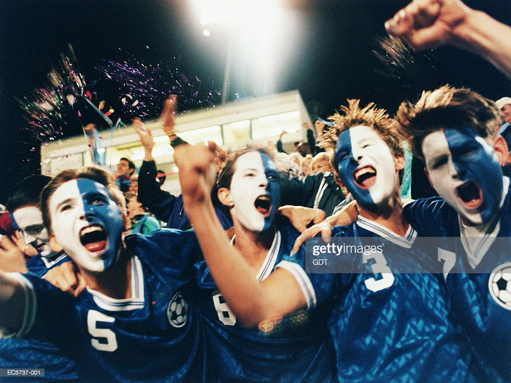 Soccer fans cheering in stadium, men with painted faces : Stock Photo