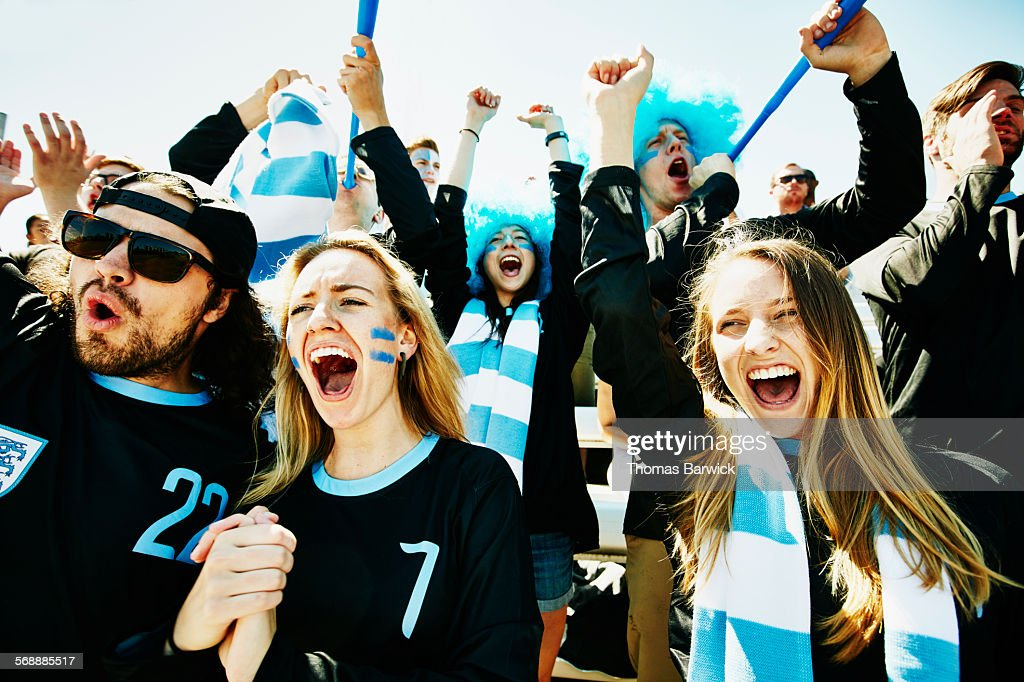 Soccer fans in stadium celebrating team victory : Stock Photo
