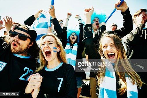 Soccer fans in stadium celebrating team victory
