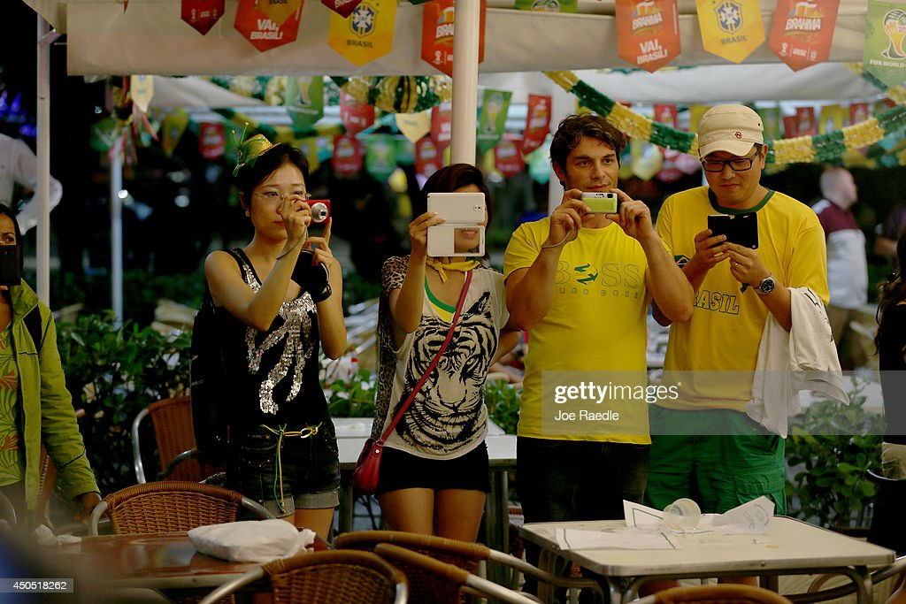 Soccer fans take pictures as anti-World Cup protestors interrupt their party at a restaurant on Copacabana beach on June 12, 2014 in Rio de Janeiro, Brazil. Brazil defeated Croatia 3-1 in the first match of 2014 FIFA World Cup today.