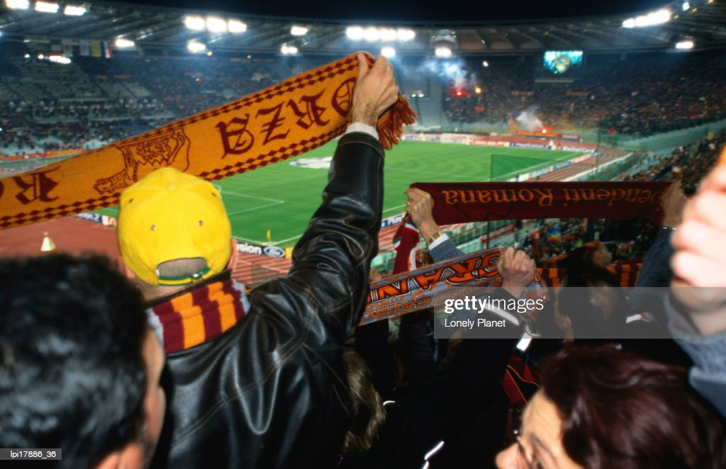 Soccer fans waving AS Roma scarves at AS Roma vs Ajax Amsterdam match at Champions League Game Stadio Olimpico, Rome, Italy