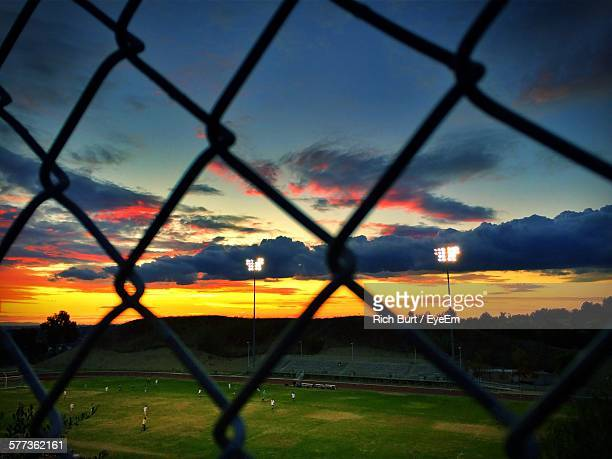 Soccer Field Against Sky Seen Through Fence During Sunset