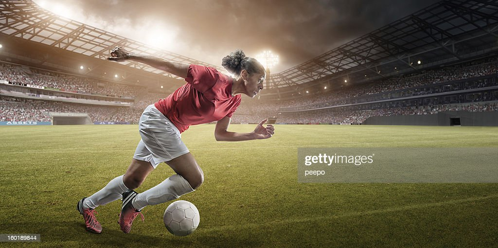 female soccer player running with ball : Stock Photo