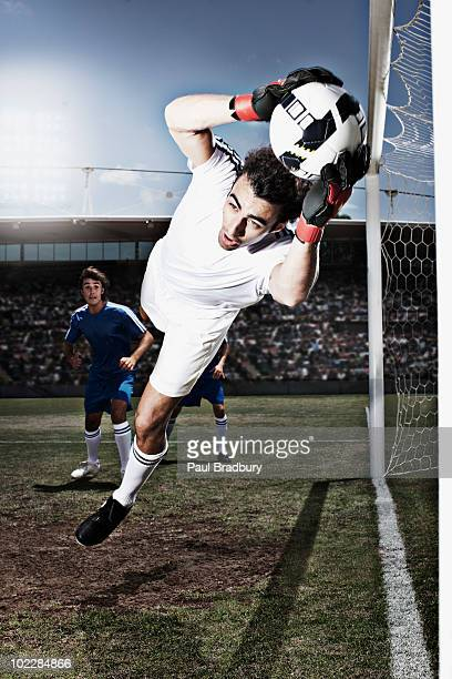 Soccer goalie catching soccer ball