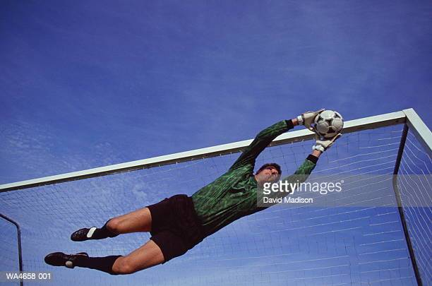 Soccer goalie in mid-air jump catching ball