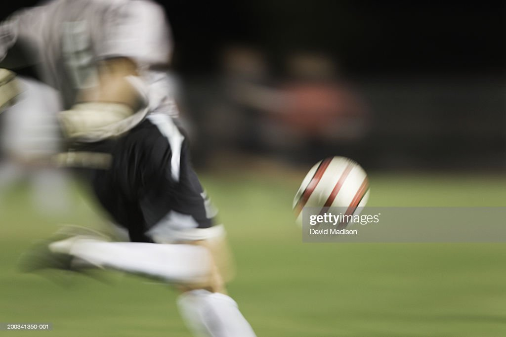 Soccer goalie kicking ball (blurred motion), low section : Stock Photo