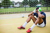 Soccer goalie sitting on pitch with ball in net
